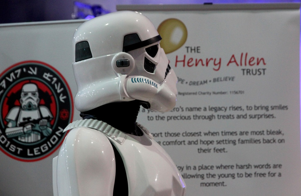 A head and shoulders profile of a 501st UK Garrison Stormtrooper standing against a Henry Allen Trust charity flag.